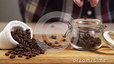 Кофейное зерно человека зажаренное в духовке ходом от руки в крупный план опарника с белой сумкой около 4K сток-видео