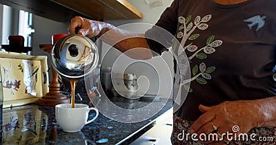 Кофе старшей женщины лить в кофейную чашку в кухне 4k видеоматериал