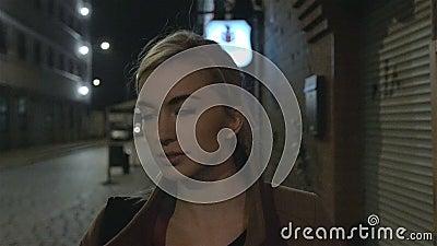 Красивая белокурая женщина в outdoors пальто идя одном на ноче зерно движение медленное акции видеоматериалы