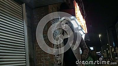 Красивая белокурая женщина в outdoors пальто идя одном на ноче зерно движение медленное видеоматериал