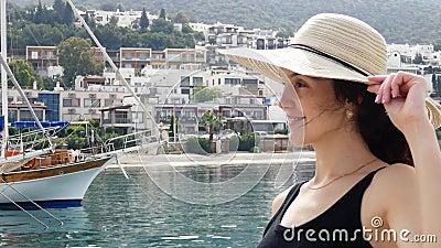 Красивая девушка в круглой шляпе лета наслаждается взглядами курортного города Яхты и шлюпки причаленные в порте в видеоматериал