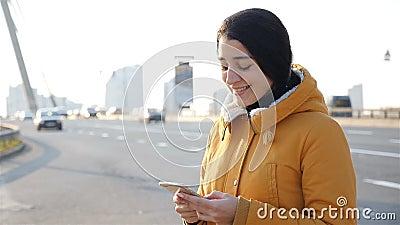 Красивая девушка пишет сообщение на смартфоне Медленное движение Дорога на заднем плане видеоматериал