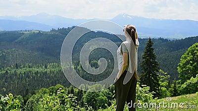 Красивая девушка стоит и смотрит на зелёные холмы и горы на расстоянии Дневной свет сток-видео