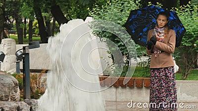 Красивая девушка с унылыми глазами стоит в дожде в парке города, около фонтана сток-видео