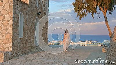 Красивая женщина идет на тротуар, останавливает для того чтобы насладиться изумительным видом на море курортный город сток-видео