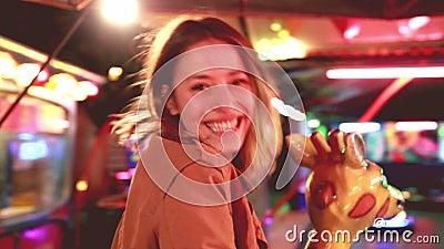 Красивая женщина имея carousel катания потехи в парке атракционов видеоматериал