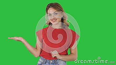Красивая женщина представляя что-то с ее руками показывая от ее левой стороны и право на зеленого экрана, ключа chroma сток-видео