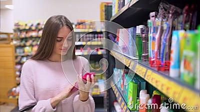 Красивая женщина смотря косметики в супермаркете Привлекательная девушка покупая косметические продукты Смотреть и выбирать сток-видео