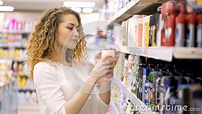Красивая женщина смотря косметики в супермаркете Продукты женщины покупая сток-видео