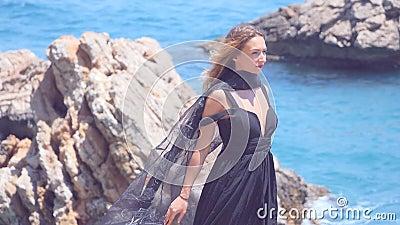 Красивая женщина с черным шарфом в элегантном черном платье видеоматериал