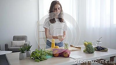 Красивая кавказская слабачка, разрывая зелень руками за стол на кухне Понятие здорового питания Фрукт акции видеоматериалы