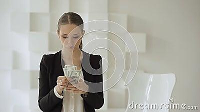 Красивая коммерсантка в официально костюме переучитывая стог долларов акции видеоматериалы