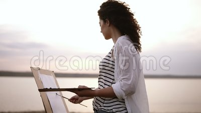 Красивая курчавая девушка рисует изображение на луге около озера используя палитру с красками и щеткой Мольберт и бумага сток-видео