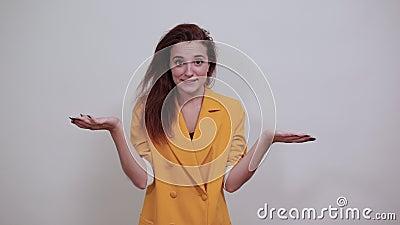 Красивая молодая женщина в желтой куртке расправляется руками, смотря счастливо акции видеоматериалы