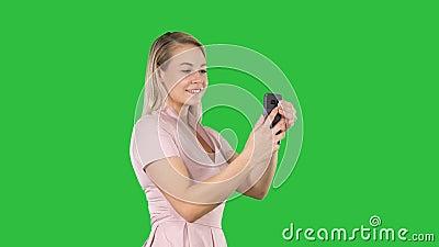 Красивая молодая женщина делая selfies на зеленом экране, ключ chroma сток-видео
