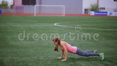 Красивая мышечная девушка в колготках и жилете делает подогрев на стадионе Перекрестная пригонка, фитнес, здоровый образ жизни сток-видео