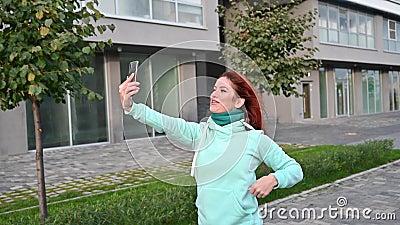 Красивая рыжеволосая женщина в маленькой толстовке ходит по улице и разговаривает по телефону Счастливая девушка расслабляется сток-видео