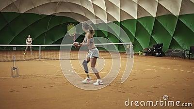 2 красивое, высокорослые девушки в одеждах спорт и бюстгальтеры играют теннис indoors Moving камера видеоматериал
