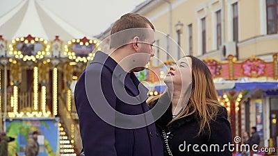 Красивые взрослые объятия пар на предпосылке carousel видеоматериал