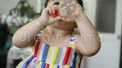 Красивые удерживание и питьевая вода маленького ребенка от освобоженной пластиковой бутылки акции видеоматериалы