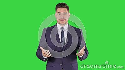 Красивый бизнесмен смотря в камере и говоря на зеленом экране, ключе Chroma акции видеоматериалы