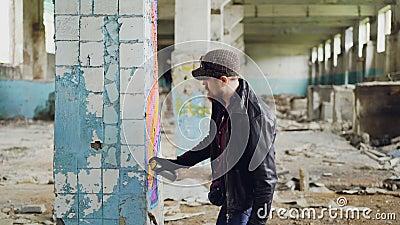 Красивый бородатый парень держит краску аэрозоля и рисуя граффити на штендере внутри просторного покинутого дома творческо сток-видео