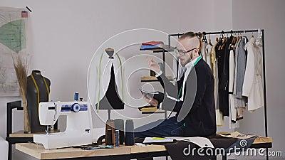 Красивый модельер сидит на таблице в студии и рисует эскизы для портняжничать новое собрание  сток-видео