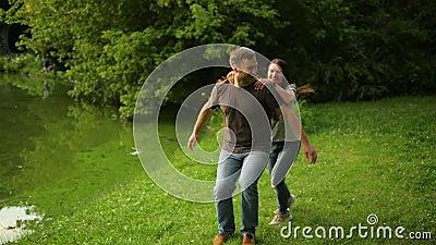 Красивый парень носит девушку на его назад Романтичная пара имеет потеху outdoors во время временени на парке города сток-видео