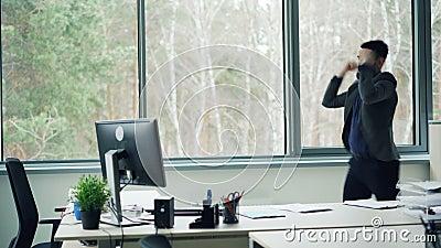 Красивый работник офиса молодого человека танцует в офисе и принимает куртку наслаждаясь свободой и хорошим настроением корпорати сток-видео