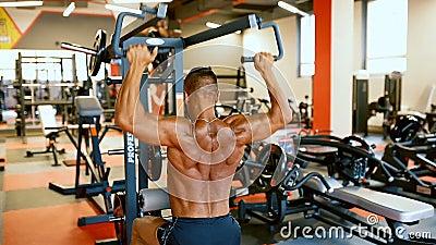Красивый спортсмен работает в центре спортзала Тренировка человека культуриста трудная muscles на машине тренировки видеоматериал