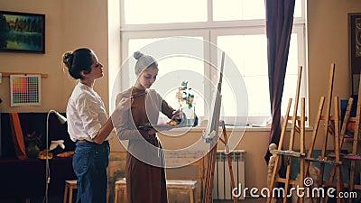 Красивый студент молодых женщин и профессиональный художник красят совместно в мастерской, учителе делят опыт видеоматериал