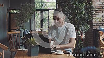 Красивый шальной эмоциональный молодой счастливый мужской бизнесмен парня показывает успех в уютном кафе Работа человека на compt сток-видео