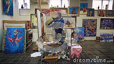 Краски художника с картиной маслом В студии, среди его собственных работ видеоматериал