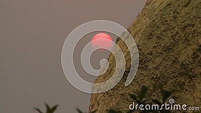 Красная установка солнца рядом с утесом акции видеоматериалы