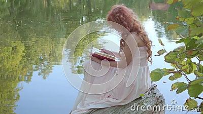 Красноголовая привлекательная кавказская девушка, читающая книгу в темно-красном обложке на берегу озера в летнем лесу Фея сток-видео