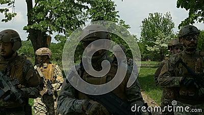 Крупный план воинской команды идя в одно образование на патруле снаружи в сельском районе пока держащ их оружи сток-видео