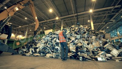 Крытый мусорный бак с кучей отходов и рабочий, наблюдающий за ним акции видеоматериалы