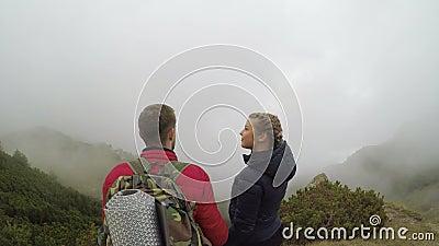 Ландшафт горы вполне плавая тумана восхищенного молодыми парами туристов держа руки и целуя концепцию туризма - видеоматериал