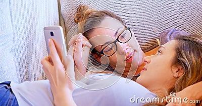 Лесбосские пары взаимодействуя друг с другом пока используя мобильный телефон 4k акции видеоматериалы