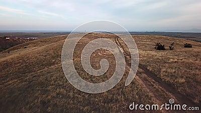 Летание над проселочной дорогой через район неорошаемого земледелия и холмы видеоматериал