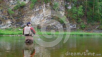 Летать на рыбалке в горной реке Взрослый человек с длинными волосами и бородой Санта-Клауса держит удочку отдых и спорт в ба видеоматериал