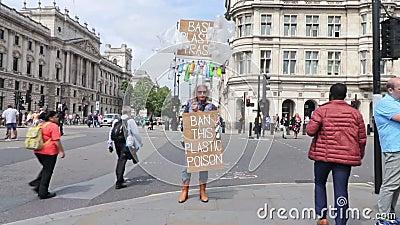 """Лондон/Великобритания - 26-ое июня 2019 - протестующий держит знаки говоря что """"погань запрета пластиковая """"и """"запрещает эту плас акции видеоматериалы"""