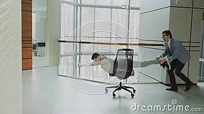 Лоток замедленного движения снял 2 смешных бизнесменов ехать стул офиса пока имеющ потеху в лобби современного делового центра акции видеоматериалы