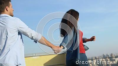 Любимая пара, держащая руки бегущей, чтобы насладиться cityscape на крыше, романтическое лето сток-видео