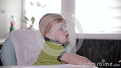 Любознательный милый младенец смотря вокруг, сидящ в стуле младенца Будьте матерью подавать ее прелестное одно годовалое с ложкой сток-видео