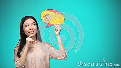 Любопытная женщина держа испанский знак флага, уча язык, образование за рубежом акции видеоматериалы