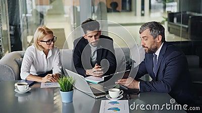Люди и женщина предпринимателей говоря в кафе смотря бумаги и ноутбук акции видеоматериалы
