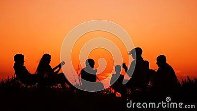 Люди сидя на пляже с лагерным костером на заходе солнца акции видеоматериалы