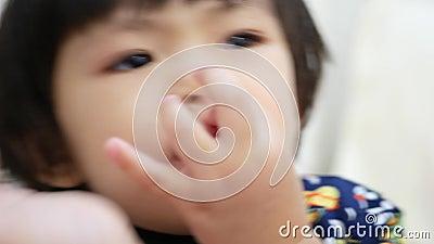 Маленькая азиатская девочка, собирающая свой нос - детская привычка / поведение видеоматериал
