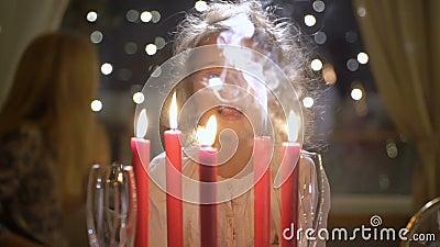 Маленькая девочка дуя вне красные свечи рождества видеоматериал